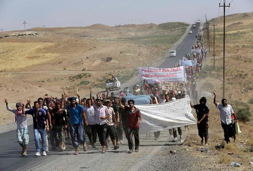 Displaced people from the minority Yazidi sect, who fled the violence in the Iraqi town of Sinjar, shout slogans as they take part in a demonstration at the Iraqi-Syrian border crossing in Fishkhabour, Dohuk province