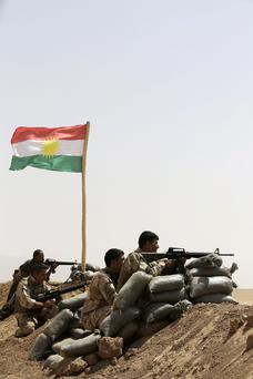 Kurdish Peshmerga fighters stand guard on the outskirts of Gwer town after Islamic State (IS) insurgents withdrew.