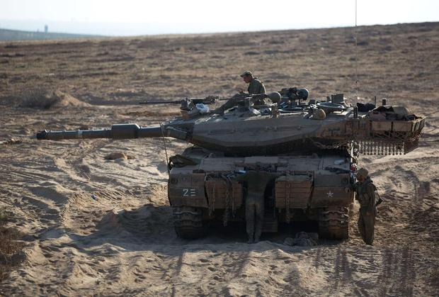 Israeli soldiers are seen around their tank next to the Israeli border with the northern Gaza Strip