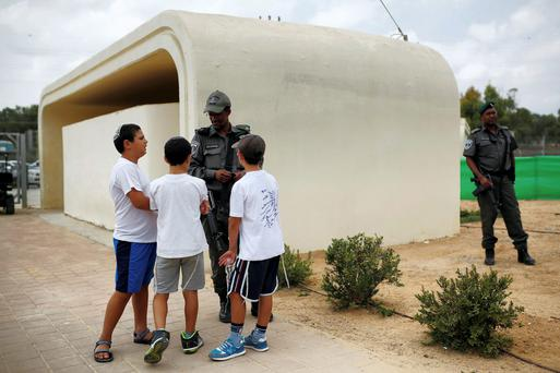Israeli children speak with a police officer as they stand next to a bomb shelter on the first day of the school year in Kibbutz Saad, outside the Gaza Strip