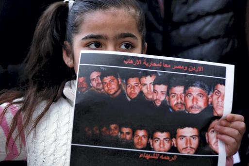 A girl holds up a poster with pictures of the 21 Egyptian Coptic Christians beheaded by Islamic State in Libya, as they gather in a gesture to show their solidarity, in front of the Egyptian embassy in Amman