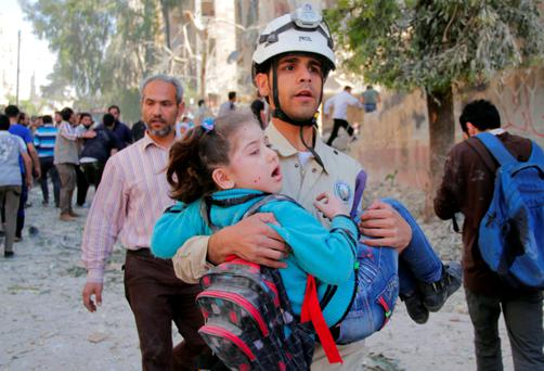 An injured schoolgirl is taken for treatment after a bomb attack on Aleppo.