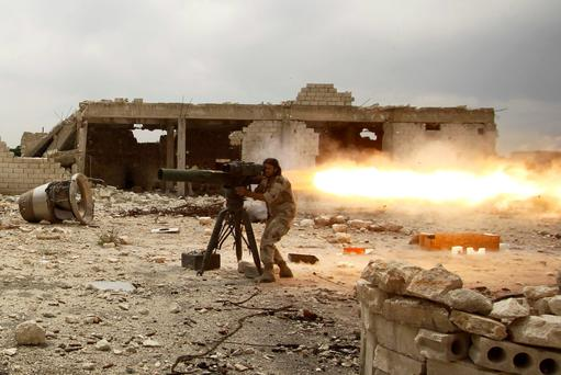 A rebel fighter of 'Al-Sultan Murad' brigade fires an anti-tank missile towards forces loyal to Syria's President Bashar al-Assad near Aleppo's international airport yesterday.