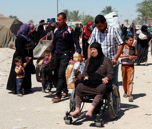 A displaced Iraqi Sunni man pushes an elderly woman in a wheelchair on the outskirts of Baghdad