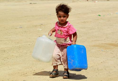 A displaced Iraqi child, who fled Anbar province due to the conflict, carries jerrycans at a makeshift camp for internally displaced persons 30wkm south of Fallujah. Photo: Getty Images