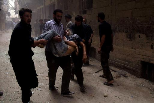 Residents carry a casualty at a site hit by what activists said were airstrikes by forces loyal to Syria's President Bashar al-Assad in Arbeen town.