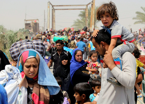 A displaced Sunni man fleeing the violence in Ramadi carries a crying child on his shoulders