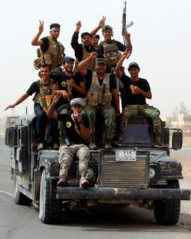 Iraqi Shiite fighters from the Popular Mobilisation units ride on a military Hummer in the town of Baiji, north of Tikrit, as they fight alongside Iraqi forces against the Islamic State (IS) jihadist group to try to retake the strategic northern Iraqi town for a second time