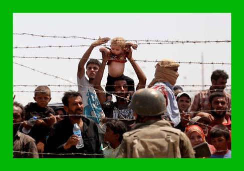Syrian refugees passing on the Syrian side of the border crossing Akcakale yesterday.