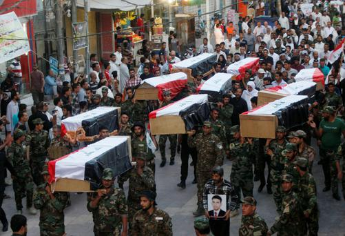 Members of Shi'ite group Asa'ib Ahl al-Haq carry the remains of Shi'ite soldiers from Camp Speicher, who were killed last summer by Islamic State militants, during the funeral ceremony in Najaf, south of Baghdad