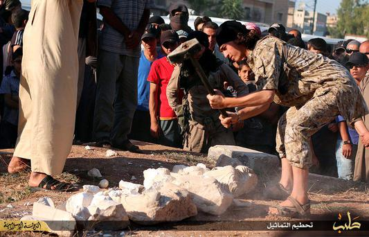 An image made available by propaganda Islamist media outlet Welayat Halab on July 2, 2015 allegedly shows an Islamic State (IS) group fighter destroying ancient artifacts smuggled from the Syrian city of Palmyra, a 2,000-year-old metropolis and an Unesco world heritage site located 215 kilometres northeast of Damascus, as other watch on in the town of Manbij, northeast of Syria's embattled northern town of Aleppo.