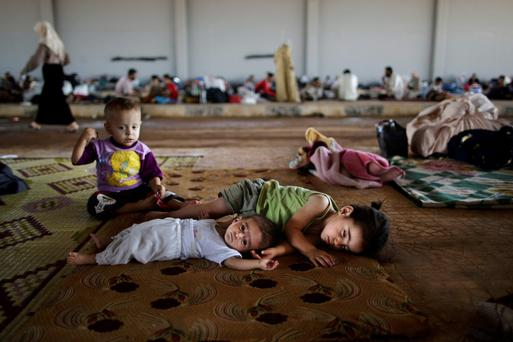 Syrian children who fled their home with their family due to fighting between the Syrian army and the rebels, lie on the ground while they and others take refuge at the Bab Al-Salameh border crossing, in hopes of entering one of the refugee camps in Turkey.