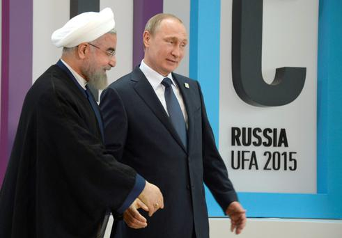 Russia's President Vladimir Putin (R) welcomes Iran's President Hassan Rouhani during the 7th BRICS summit in Uf