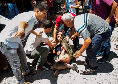 Rescuers help a survivor of the deadly explosion that killed dozens of people and injured many others in the southeastern Turkish city of Suruc.