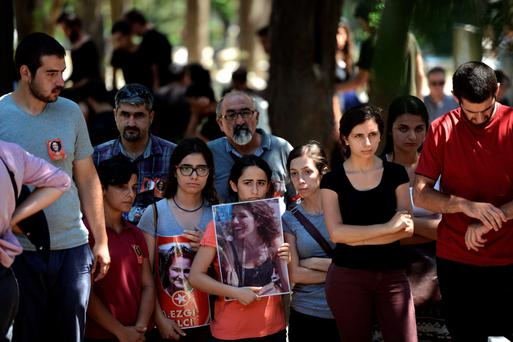 Mourners hold posters of people who were killed during a suicide bomb attack as they attend the funeral of victim Ece Dinc in Istanbul.