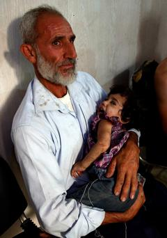A Syrian man comforts a wounded child at at a make-shift medical centre in Douma on the northeastern outskirts of the Syrian capital Damascus yesterday.