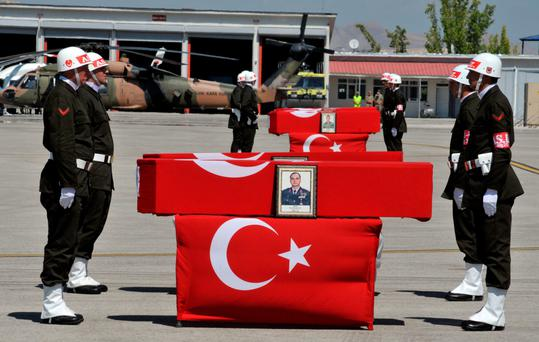 A guard of honour flanks the flag-draped coffins of Turkish soldiers killed in an attack by PKK militants during a ceremony at a military base in the eastern city of Van, Turkey, yesterday