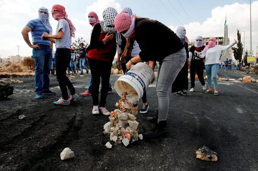 DETERMINATION: A female Palestinian protester drops stones to the ground during clashes with Israeli troops near the Jewish settlement of Bet El, near the West Bank city of Ramallah