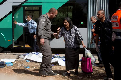 An Israeli border police officer escorts a woman at the scene of a shooting attack in Jerusalem, where two Palestinians boarded a bus and began shooting and stabbing passengers, killing two