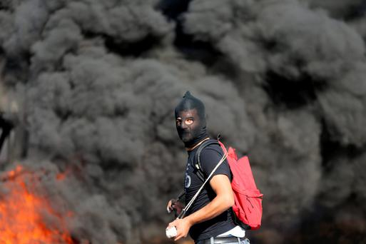 A Palestinian protester clashes with Israeli troops near the Jewish settlement of Beit El, near Ramallah