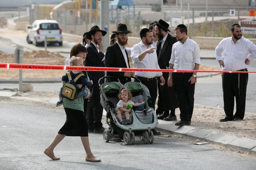 Onlookers stand at the scene of a stabbing, west of Jerusalem, in the town of Beit Shemes.