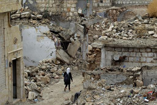 A school girl walks past damaged buildings in the rebel-controlled area of Maaret al-Numan town in Idlib province, Syria yesterday