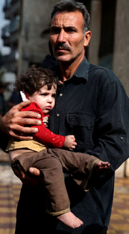 A Syrian man carries an injured child at a site hit by missiles fired by government forces in Damascus