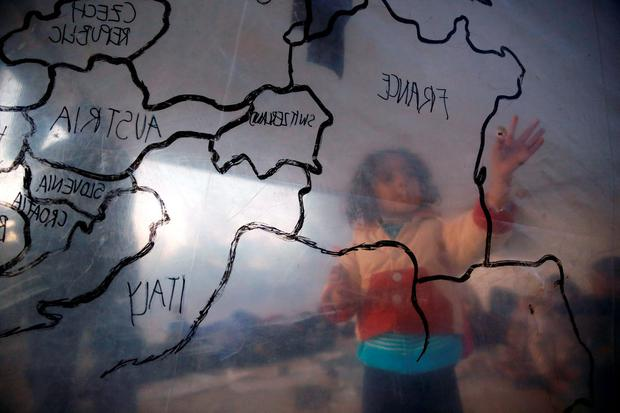 A refugee child looks at a map of Europe inside a make-shift tent at a refugee camp close to a registration center on Lesbos