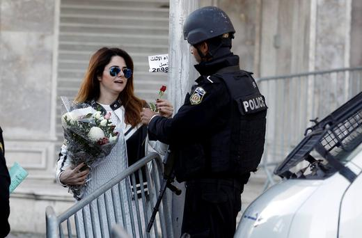 Tunisian woman gives flowers to a policeman in Tunis, Tunisia after 13 people were killed in a suicide bombing.