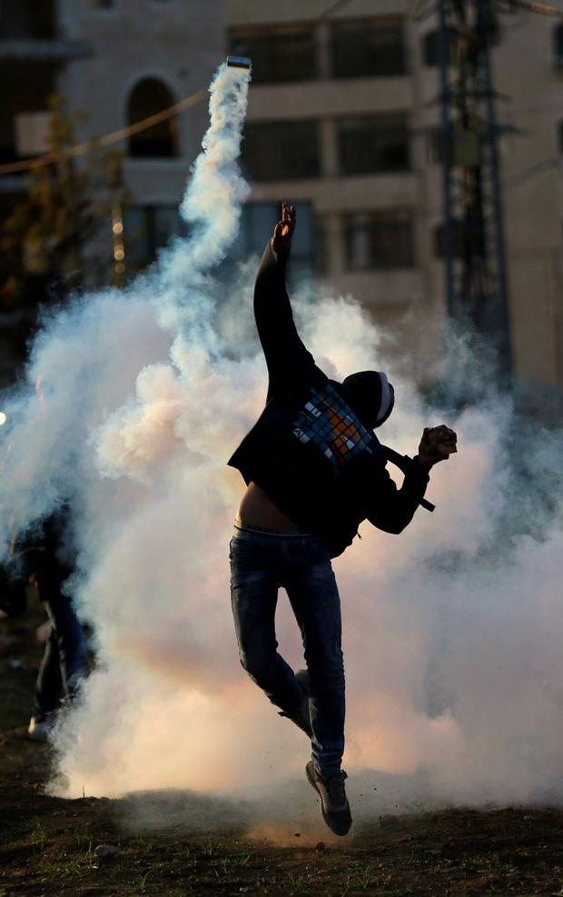 A Palestinian protester returns a tear gas canister fired by Israeli troops during clashes near the Jewish settlement of Bet El, near the West Bank city of Ramallah