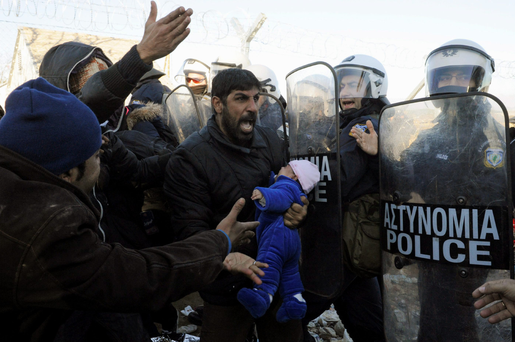 A stranded migrant holding a baby shouts next to a Greek police cordon following scuffles at the Greek-Macedonian border, near the village of Idomeni, Greece.