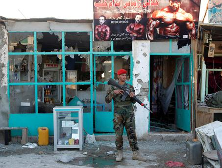 An Afghan National Army soldier stands guard in front of a shop burned during the Taliban attack on Kandahar Airport. Photo: Reuters