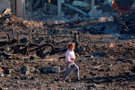 A girl walks over debris at a site hit by one of three truck bombs, in the YPG-controlled town of Tel Tamer, Syria yesterday. The death toll from a triple truck bomb attack in a town in northeastern Syria yesterday had risen to 50 to 60 people.