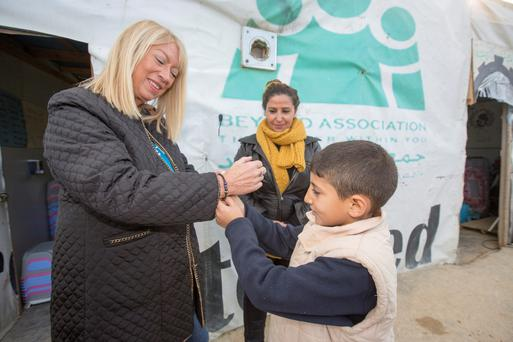 Unicef goodwill ambassador Anne Doyle receives a gift from Ali (9), and right, having fun in a makeshift classroom