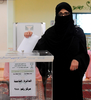 A Saudi woman casts her ballot at a polling station in the coastal city of Jeddah