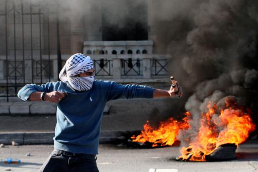 A Palestinian protester uses a slingshot to fire stones during clashes with Israeli security forces at the main entrance of the West Bank city of Bethlehem yesterday