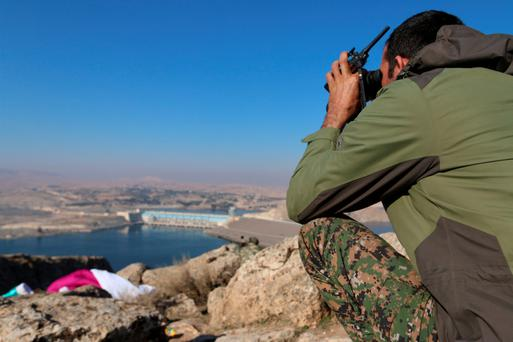 A Syrian fighter takes a position overlooking the Tishrin dam after it was captured from Islamic State militants, south of Kobani in Syria Photo: Reuters