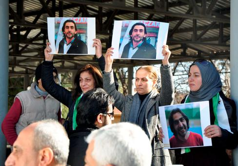 Women hold pictures of film maker Naji Jerf, who was killed on December 27, during his funeral in Gaziantep . He was a trenchant critic of Isil. Photo: Getty