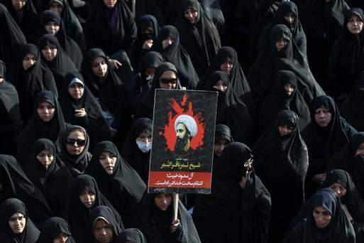 An Iranian woman holds up a poster showing Sheikh Nimr al-Nimr, a prominent opposition Saudi Shiite cleric who was executed last week by Saudi Arabia, during a protest against his death in Tehran, Iran
