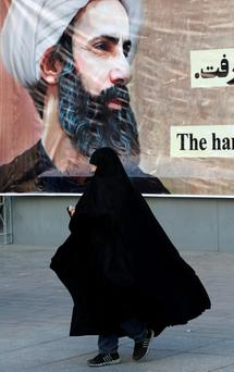 An Iranian woman in Tehran walks past a portrait of Sheikh Nimr al-Nimr, a prominent opposition Saudi Shiite cleric who was executed by Saudi Arabia last week. Photo: AP