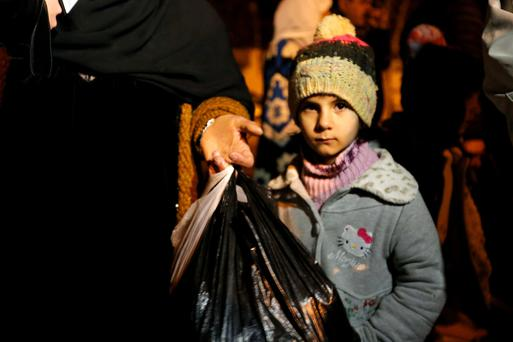 A Syrian girl waits to depart Madaya with her family, whose members say they have received permission from the Syrian government to leave the besieged town.