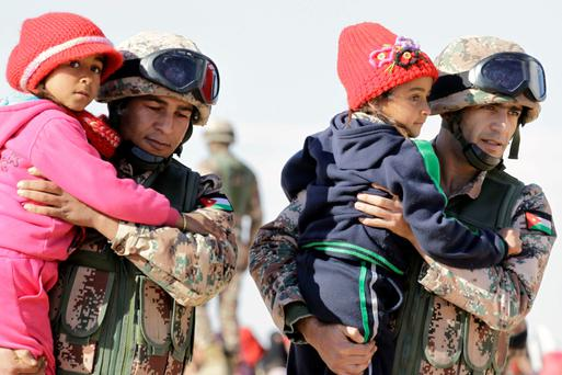 Jordanian security forces help Syrian girls after crossing from Syria into Jordan, near the town of Ruwaished, east of the Jordanian capital Amman.