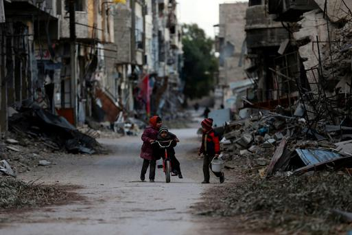 A girl pushes a boy on a bicycle past damaged buildings in Damascus, Syria. Photo: Reuters/Bassam Khabieh