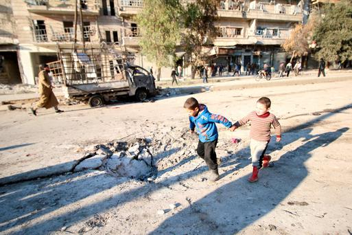 Boys run near a hole in the ground after airstrikes by pro-Syrian government forces in the rebel held al-Sakhour neighborhood of Aleppo, Syria.