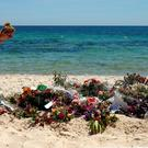 A tourist examines flowers left in tribute at the scene of the Isil massacre of holidaymakers, three of them Irish, in Sousse, Tunisia last year