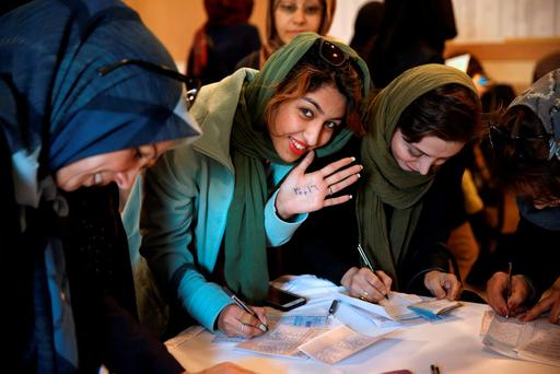 GET THE VOTE OUT: A young Iranian voter in Tehran shows her hand with the numbers '30+16' written on it — a reformist slogan urging people to vote — as she fills out her ballot paper in a polling station in Iran this weekend. Photo: Vahid Salemi