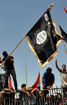 Masked Sunni protesters wave Islamist flags while others chant slogans at an anti-government rally in Fallujah, Iraq, in 2013