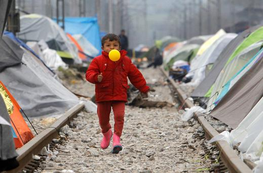 A refugee boy with a balloon in his mouth runs along railway tracks at a makeshift migrant camp in the northern Greek border post of Idomeni