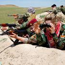 Iraqi Kurdish female fighter Haseba Nauzad (red beret), and Yazidi female fighter Asema Dahir (camouflage cap) aim their weapons during a deployment near the frontline of the fight against Islamic State militants in Nawaran near Mosul, Iraq. Photos: Reuters
