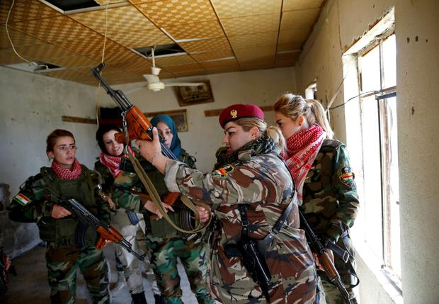 Iraqi Kurdish female fighter Haseba Nauzad (2nd R), 24, holds her weapon as she is surrounded by comrades at a site during a deployment near the frontline of the fight against Islamic State militants in Nawaran near Mosul